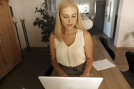 Young blond woman using laptop at home - KMKF00418