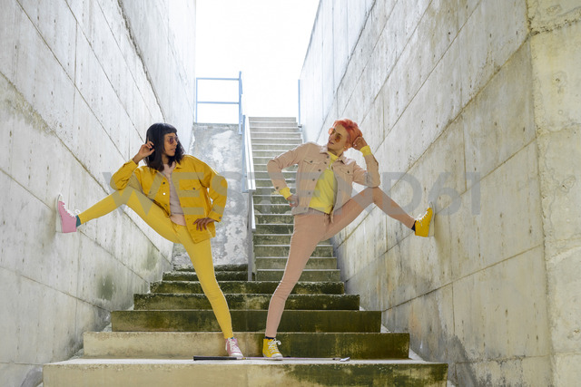 Two alternative friends posing on steps, wearing yellow and pink jeans clothes - AFVF01015