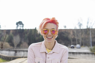 Portrait of young laughing woman, sun glasses and pink jeans jacket - AFVF01030