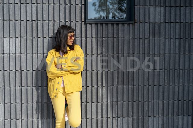 Young woman wearing yellow jeans clothes, looking away - AFVF01033