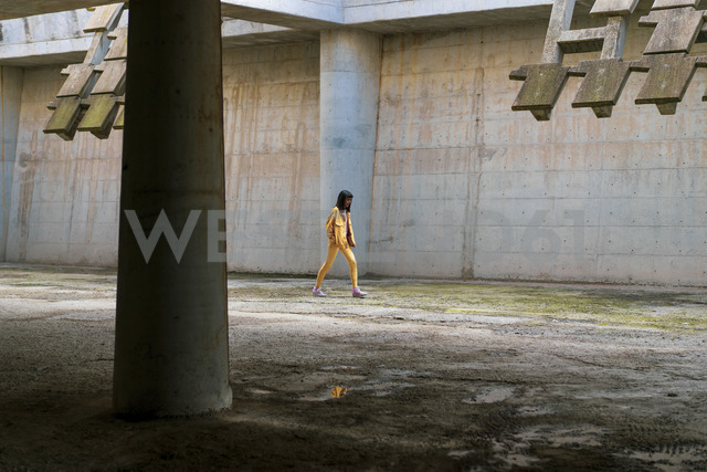 Young woman wearing yellow jeans clothes, walking - AFVF01039