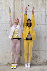 Two alternative friends wearing yellow and pink jeans clothes, posing, raising arms - AFVF01045