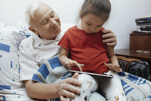 Grandfather and granddaughter with digital tablet at home - AZF00056