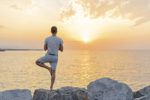 Spain. Man doing yoga during sunrise on rocky beach, tree position, rear view - AFVF01066