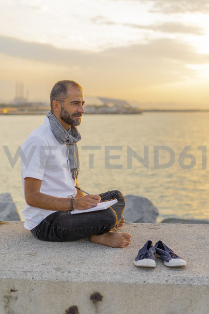 Spain. Man writing on a notebook during sunrise - AFVF01069