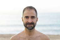 Portrait of happy man on a beach in the evening - AFVF01075