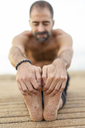 Spain. Man doing yoga on the beach in the evening, stretching legs, hands and soles of feet - AFVF01081