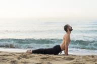 Spain. Man doing yoga on the beach in the evening, cobra pose - AFVF01084