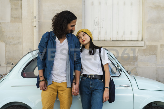 Young couple in love standing at small car - AFVF01097