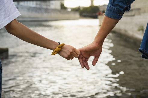 France, Paris, close-up of couple holding hands at river Seine - AFVF01106