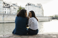 France, Paris, happy young couple sitting on a wall at river Seine - AFVF01109