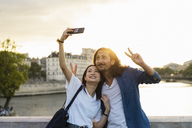 France, Paris, happy young couple taking a selfie at river Seine at sunset - AFVF01121