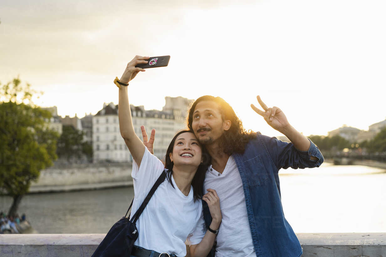 France, Paris, happy young couple taking a selfie at river Seine at sunset - AFVF01121 - VITTA GALLERY/Westend61