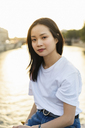 France, Paris, portrait of young woman at river Seine at sunset - AFVF01124