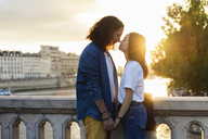 France, Paris, affectionate young couple at river Seine at sunset - AFVF01133