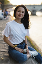 France, Paris, portrait of smiling young woman with camera at river Seine at sunset - AFVF01145