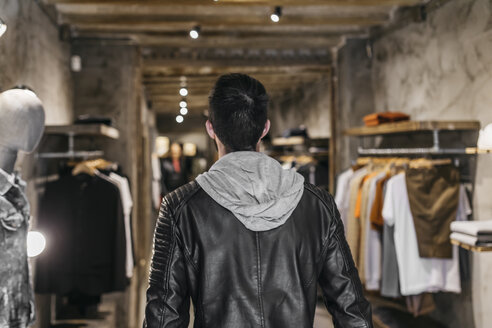 Rear view of man in modern menswear shop - JRFF01697