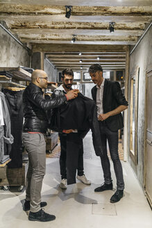 Designer and stylist in modern menswear shop offering new collection to man - JRFF01700