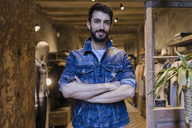 Portrait of smiling man wearing denim jacket in menswear shop - JRFF01715