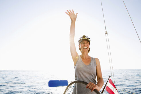 Smiling woman steering boat - ISF17385