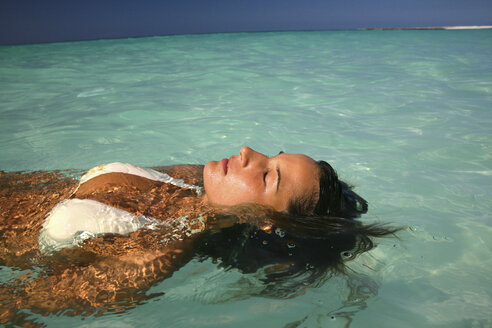 Woman floating in tropical water - ISF17436