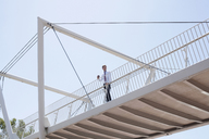 Businessman walking on urban bridge - ISF17493