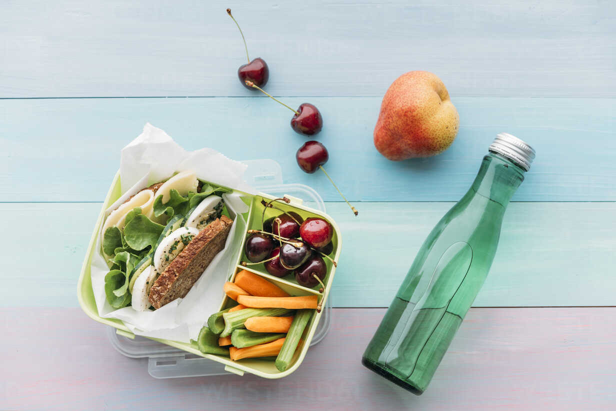 Healthy school food in a lunch box, vegetarian sandwich with cheese, lettuce, cucumber, egg and cress, sliced carrot and celery, cherries and pear - IPF00465 - Ina Peters/Westend61