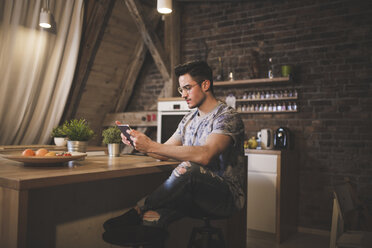 Young man using tablet in kitchen at home - AWF00124