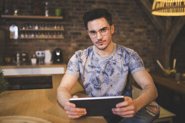 Portrait of young man using tablet in kitchen at home - AWF00127
