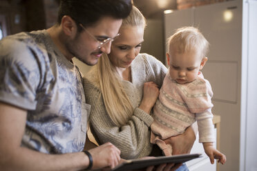 Young parents using tablet at home with their baby girl - AWF00130