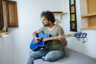 Spain, Man playing bass guitar in his room - KIJF01971