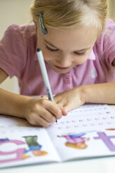 Smiling little girl writing numbers in exercise book - JFEF00893