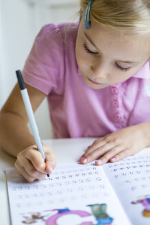 Little girl writing numbers in exercise book - JFEF00896