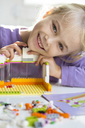 Portrait of happy little girl playing with building bricks - JFEF00899