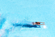 Woman diving underwater in swimming pool - SMAF01066