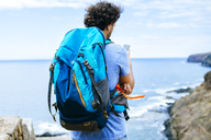 Spain, Canary Islands, Gran Canaria, Close-up of man with backpack using mobile phone - KIJF01974