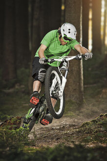 Mountain biker riding on back wheel through forest - ISF18041