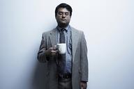 Studio portrait of businessman holding mug of tea - ISF18110