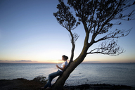 Young woman leaning on tree at dusk - ISF18134