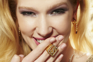 Close up portrait of young woman wearing diamond signet ring - ISF18164