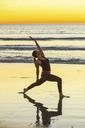 Woman practicing yoga on beach - ISF18221