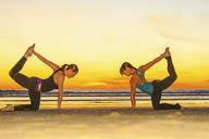 Women practicing yoga on beach - ISF18224
