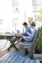 Couple on patio with laptop and mobile, Breezy Point, Queens, New York, USA - ISF18329