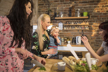 Happy female friends with cell phone and baby girl preparing dinner together - AWF00156