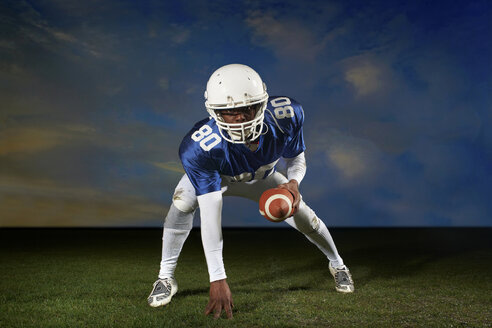 American football player leaning forward with hand on grass - ISF18415