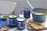 Meal with mugs of leek and potato soup with bread - ISF18439