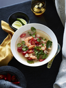 Bowl of Tom yum soup with herb garnish - ISF18442
