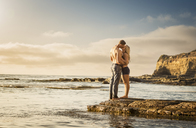 Young couple kissing on rocks, Sunset Cliffs, San Diego, California, USA - ISF18472