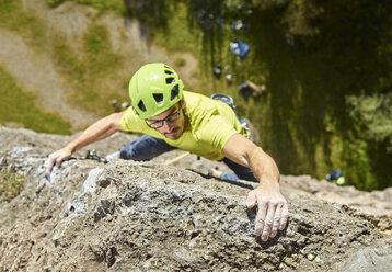 Austria, Innsbruck, Hoettingen quarry, man climbing in rock wall - CVF01008