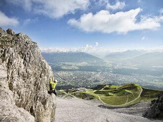 Austria, Innsbruck, Nordkette, man climbing in rock wall - CVF01017